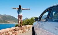 carefree tourist stands on chapmans peak drive with arms outstretched in freedom girl pose with rent